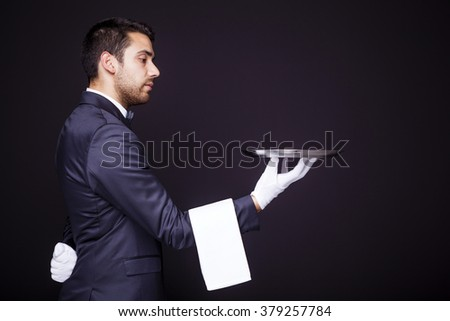 Waiter holding an empty silver tray on black background