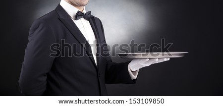 Waiter holding empty silver tray over black background - stock photo