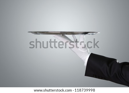 Waiter holding empty silver tray over gray background with copy pace