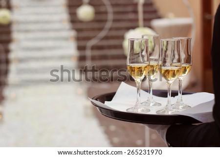 Waiter holding four glasses of wine - stock photo