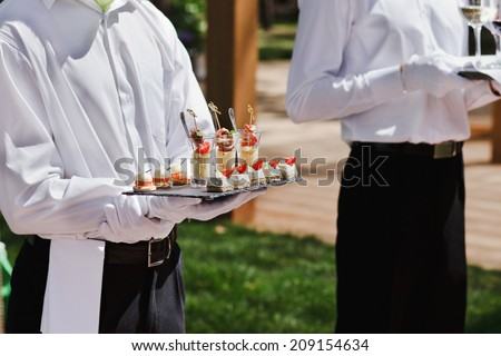 waiter holding plate with appetizer