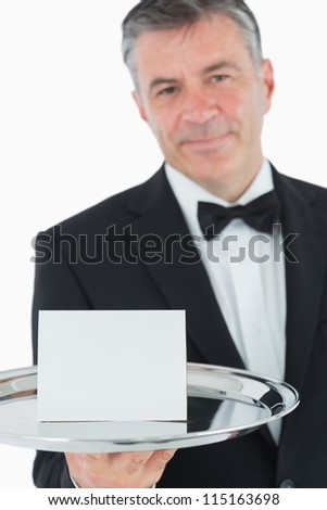 Waiter holding silver tray with white paper