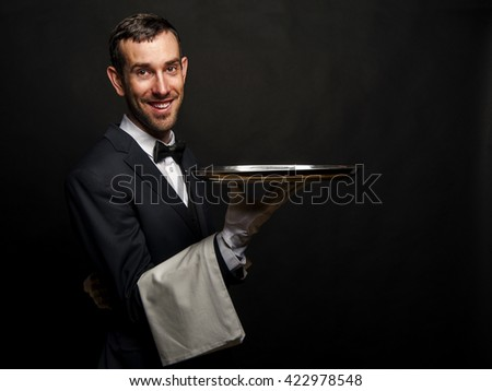Waiter in black suit holding tray over black background. - stock photo