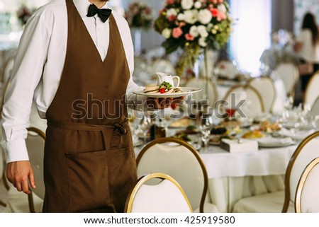 Waiter in the brown clothes on the wedding - stock photo