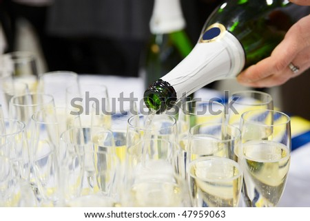 Waiter is pouring sparkling wine in flutes - stock photo