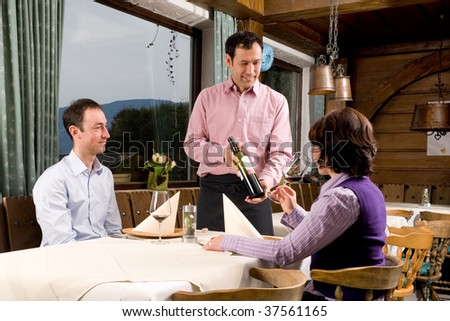 Waiter is serving some wine in a little restaurant - stock photo