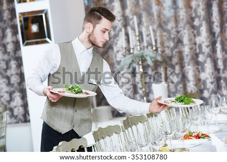 Waiter occupation. Young man with food on dishes servicing during catering in restaurant - stock photo