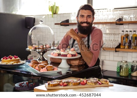 Waiter posing with cakes in the cafe