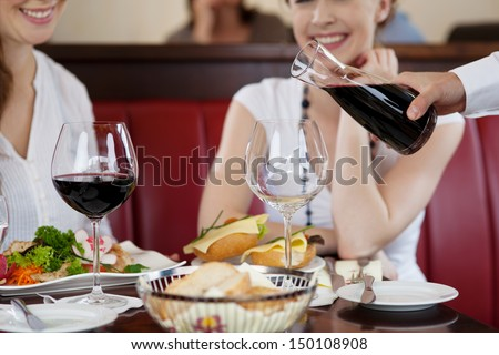 Waiter pouring red wine from a carafe at a restaurant for two young women seated at a table with their food - stock photo