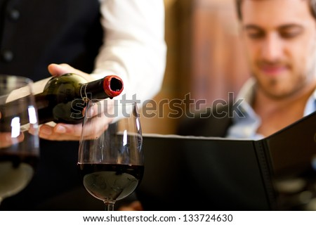 Waiter pouring red wine to a man - stock photo