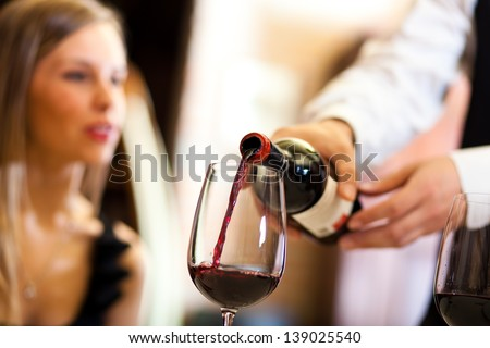 Waiter pouring red wine to a woman  - stock photo