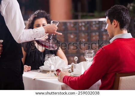 Waiter pouring red wine to couple