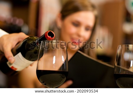 Waiter pouring wine in a glass - stock photo