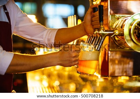Waiter pours beer in a pub