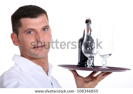 Waiter serving a bottle of beer - stock photo
