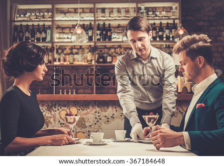 Waiter serving a desert to guests at restaurant. - stock photo