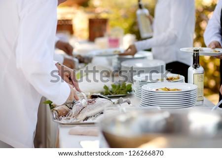 Waiter serving a tasty fish baked in salt - stock photo