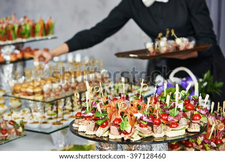 Waiter serving catering table - stock photo