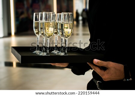 Waiter serving champagne on a tray in restaurant - stock photo