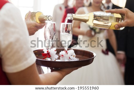 Waiter serving champagne to bride and groom - stock photo