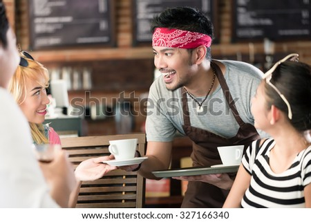 Waiter serving coffee in Asian cafe to women and man offering the drinks on a tray - stock photo
