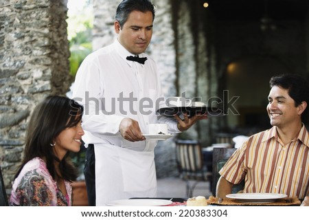 Waiter serving coffee to guests - stock photo