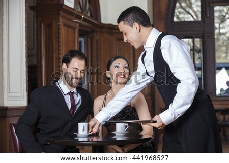 Waiter Serving Coffee To Tango Couple Sitting In Restaurant