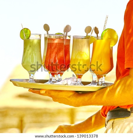 Waiter serving drinks / cocktails on the beach - stock photo