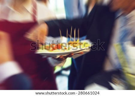 Waiter serving food on a plate during wedding evening, defocused with radial zoom blur, vintage retro instagram effect added - stock photo