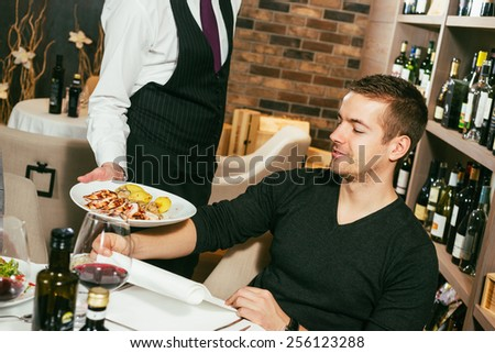 Waiter serving food to a customer - stock photo