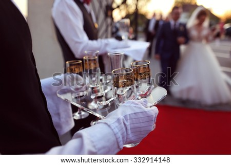 Waiter serving glasses of champagne - stock photo