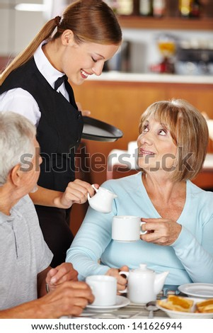 Waiter serving senior woman milk to coffee in coffee shop - stock photo