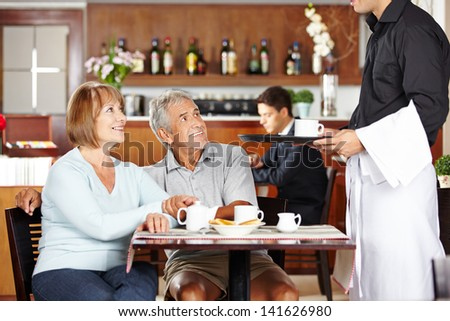 Waiter serving two seniors in a coffee shop for breakfast - stock photo