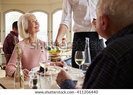 Waiter Serving Wine To Senior Couple In Restaurant - stock photo