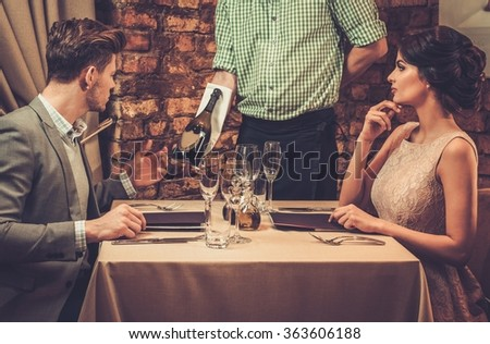 Waiter showing a sparkling wine bottle to customers.  - stock photo