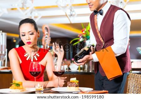 Waiter showing bottle of wine in restaurant - stock photo