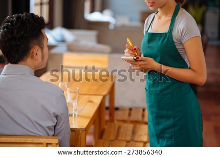 Waiter taking order from her customer in a restaurant - stock photo