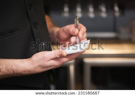 Waiter taking order in his notepad in a bar