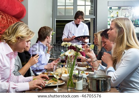 Waiter taking orders from a group of dinner guests at a restaurant