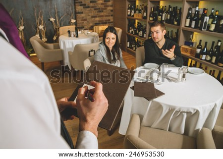 Waiter taking orders in a restaurant - stock photo