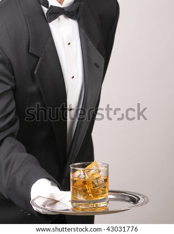 Waiter wearing a tuxedo leaning in to serve a glass of whiskey on a silver tray. Vertical format showing the mans torso only over a gray background with copy space. - stock photo