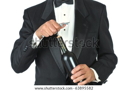 Waiter wearing a tuxedo opening a wine bottles isolated over white. Close up shot of torso only. - stock photo
