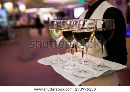 Waiter welcomes guests with sparkling wine - stock photo