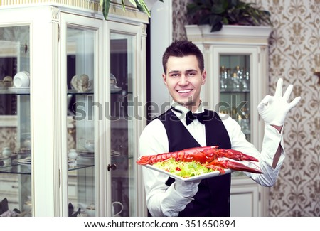 waiter with a tray of food in the restaurant hall - stock photo