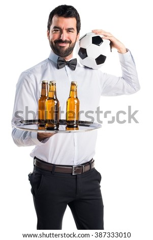 Waiter with beer bottles on the tray holding a soccer ball - stock photo