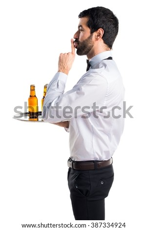 Waiter with beer bottles on the tray making silence gesture - stock photo