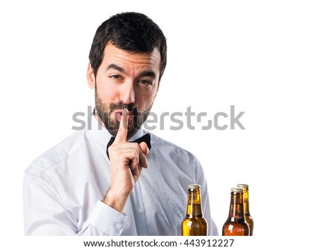 Waiter with beer bottles on the tray making silence gesture
