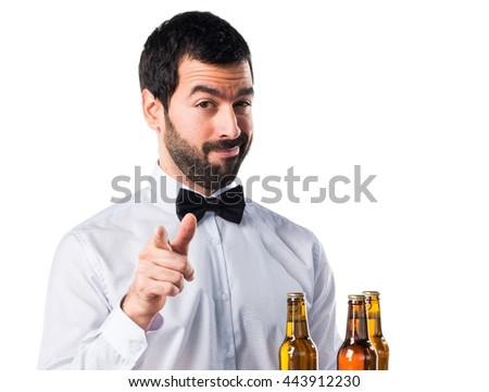 Waiter with beer bottles on the tray pointing to the front