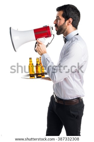 Waiter with beer bottles on the tray shouting by megaphone - stock photo