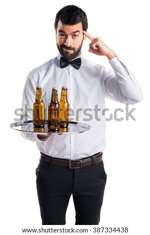 Waiter with beer bottles on the tray thinking